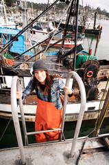 Woman in fishing gear on ship
