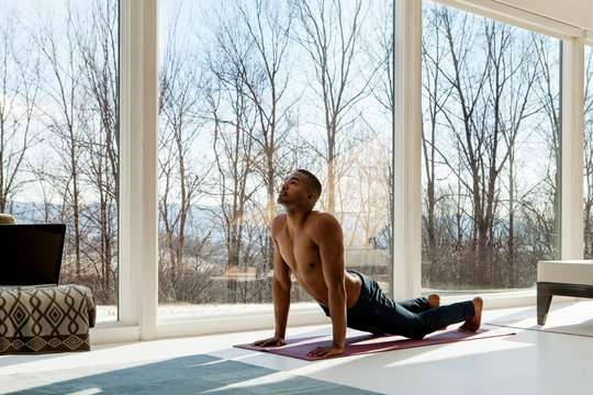 Young man exercising in living room
