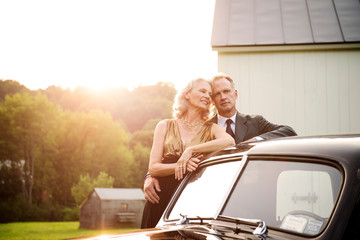 Elegant mature couple standing by retro style car