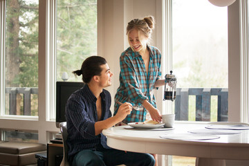 Young couple eating breakfast in dining room