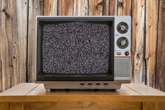 Vintage portable television on old table with wood wall and static screen.