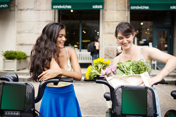 Woman and teenage girl (16-17) using bike share after grocery shopping