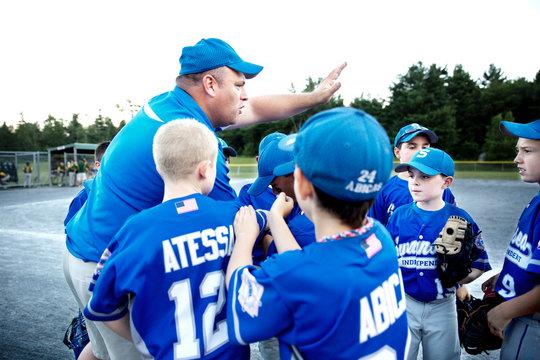 Coach congratulating little league team (8-9)  in huddle