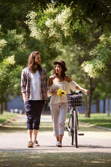 Young couple walking along street with bicycle