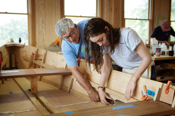Shipbuilder teaching young woman his craft