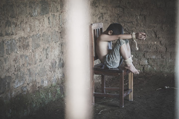 The boy was tied at the corner of the abandoned house, hostage, Stop violence against children and trafficking.
