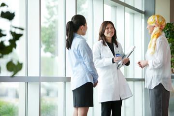 Doctor talking with patients in corridor