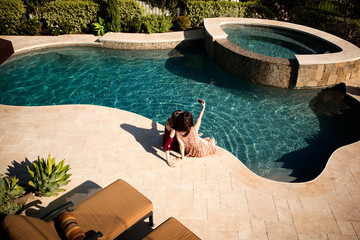 High angle view of young female photographing themselves by swimming pool