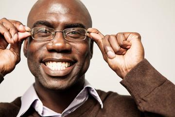 Portrait of smiling man adjusting eyeglasses