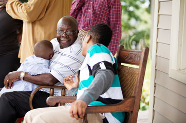 Teen boy talking with grandfather holding grandson at family reunion