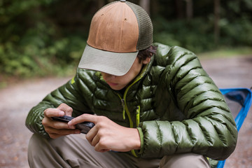 Teenage boy texting in forest
