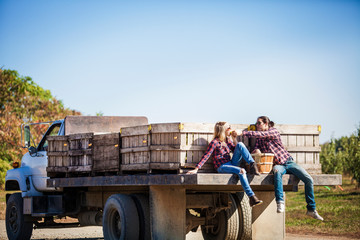 Two female friends sitting on back of truck