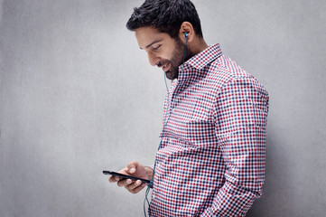 Mid-adult man texting and listening to music