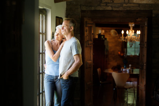 Mature couple looking through window at home