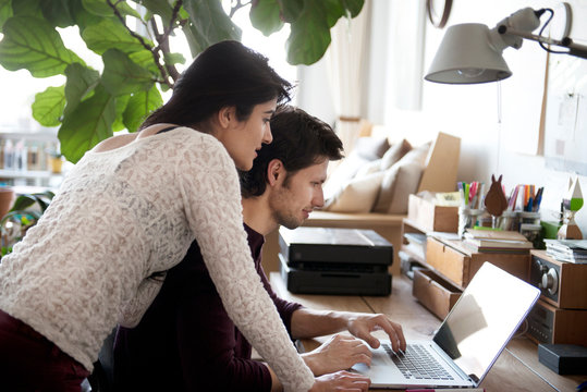 Woman looking over mans shoulder at laptop