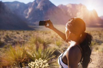 Young woman photographing in desert,