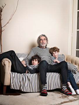 Portrait of father with sons sitting on sofa at home
