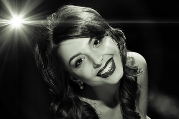 Happy beautiful brunette with red lips and long curly hair, black and white photography in retro style