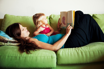 Mother reading to daughter (18-23 months) on couch