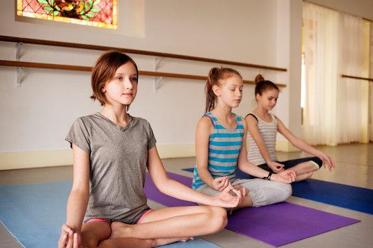 Three girls (10-11) doing yoga