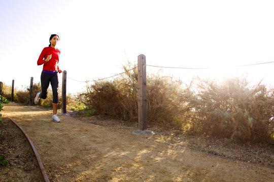 Female athlete running on ocean path