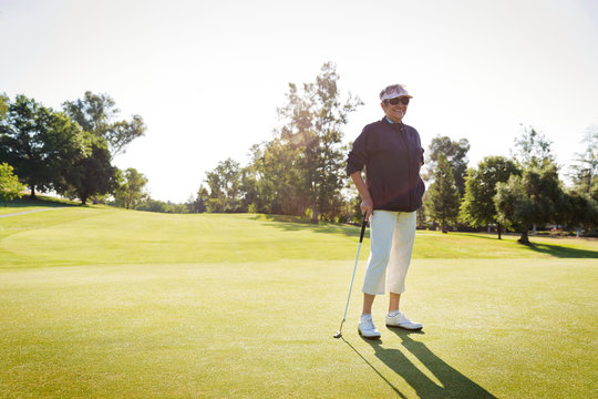 Portrait of female golfer standing on golf course
