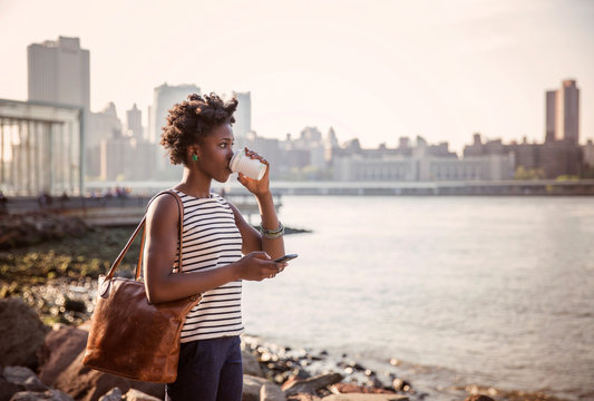 Young woman with bag drinking coffee outdoors