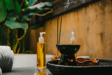 Outdoor spa salon. Massage oils, burning incense sticks with smoke, towels, flowers on wooden ...