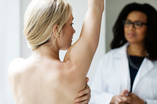 Naked woman with raised arm and doctor in background,