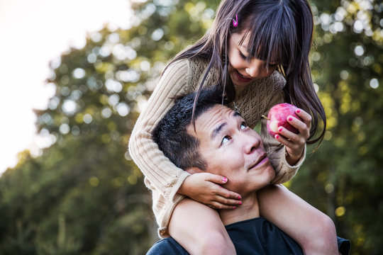 Girl (6-7) sharing apple with dad