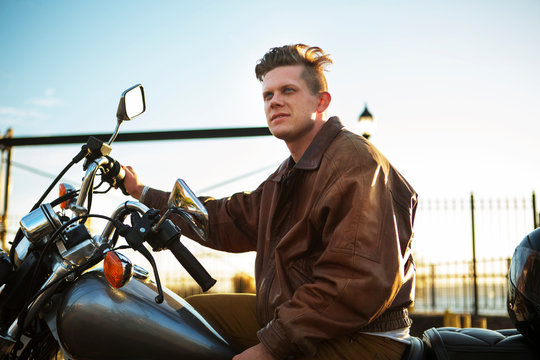 Young man on motorcycle in sunset