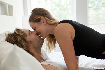 View of mid adult couple kissing in bed