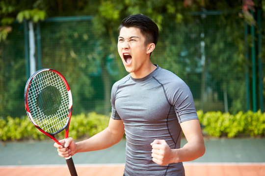 young asian male tennis player celebrating success