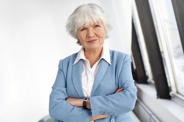 Age, maturiy, job, style and elegance concept. Waist up shot of skilled female boss in her sixties posing by window at her office, keeping arms crossed, looking at camera with serious confident smile