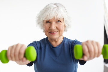 Active energetic happy elderly Caucasian female with gray hair enjoying physical exercises indoors,...