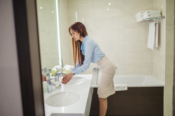 Young woman dressed in formal style getting ready for work doing morning hygienic routine, looking at her reflection in the mirror while washing hands in the bathroom