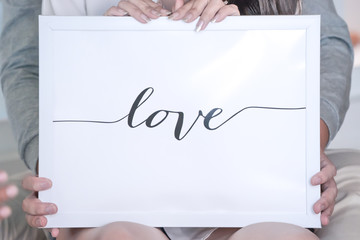 LOVE letter in the white frame and background, Hold by bride and groom behind.