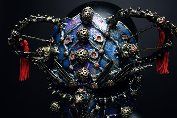 Iron demon mask with precious stones on dark background