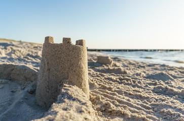 Fototapete -  Sandburg am Strand mit Meer