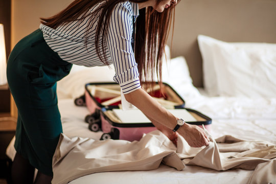 Female hotel guest in formal wear packing her suitcase, leaving hotel for airport, back to sweet home.