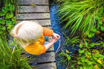 Blonde Boy Playing At Small Creek In Swedish Nature