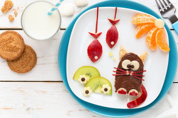 Fun Food for Kids - cute funny cat shaped toast covered with chocolate spread and decorated with fish shaped apple pieces, kiwi slices and tangerines