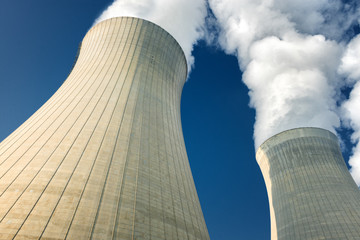 power plant cooling towers steaming on dark blue sky background