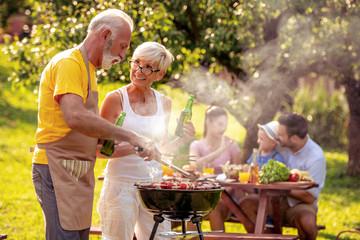 Senior couple make barbecue