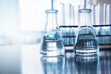 two clear flask with water in front of test tube in education chemistry science laboratory background