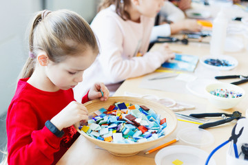 The girl is engaged in creating a mosaic in a creative workshop.