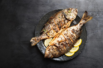 Tasty grilled fish dorado with  lemon on kitchen table.