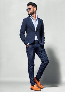 Elegant young handsome man in suite wearing glasses. Studio fashion portrait.