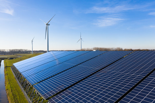 Solar panels and wind turbines generating eco friendly green energy for a better environment near Waalwijk, Noord-Brabant, Netherlands.
