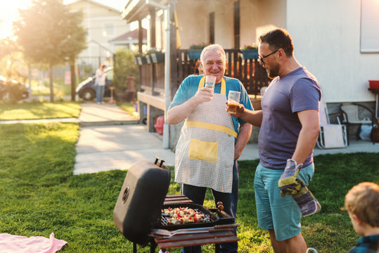Cheerful father and son drinking beer while standing next to grill in backyard at summer. Family gathering concept.